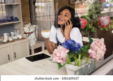 Black lady having a laugh while on the phone with a coffee in her hand.
