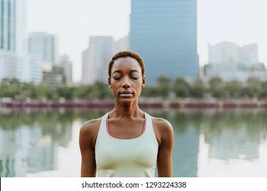 Black lady making a meditation at a park
