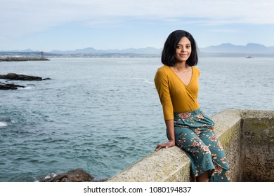 Black lady sitting on a rock wall looking straight into the camera.