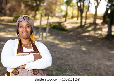 Black lady standing in the forest wearing her traditional clothes.