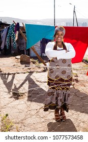 Black lady in a township wearing her traditional clothes.