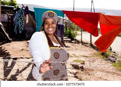 Black lady wearing her traditional clothes while at her township house.