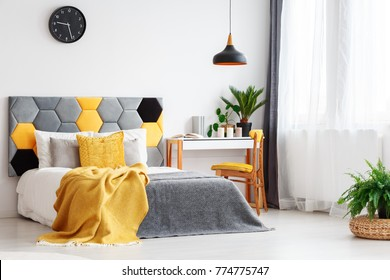 Black lamp above bed with yellow pillow and bedhead against a wall with clock in grey bedroom interior with plants and chair at desk