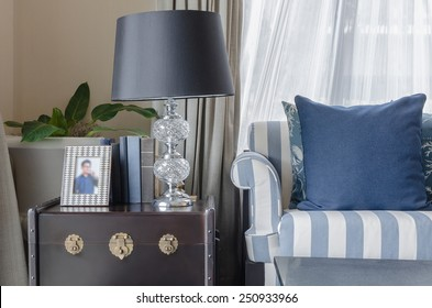 black lamp with books on wooden table in living room