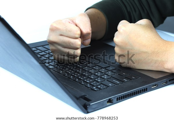 black laptop with man's fist hand isolated on white background, in concept of angry worker, work under pressure, unhappy business man