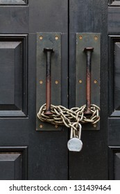 A black large door closed with a chain and a lock
