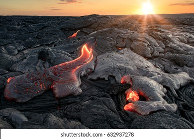 Black lava field with hot red orange Lavaflow at sunset background