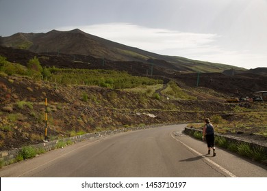 black lava fields flowing from mount Etna steep slopes with gravel stones thrifty overgrown by strong survival pioneer plants, woman walking over road shoulder towards the cable car entrance