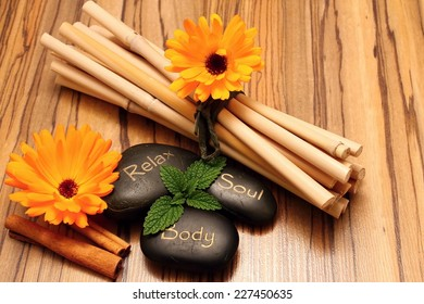 Black lava stones and flower blooms on wooden boards with cinnamon and bamboo on background