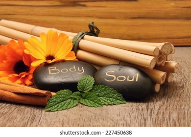 Black lava stones and flower blooms on wooden boards with cinnamon and bamboo in background