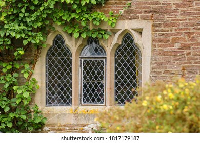 Black leaded windows in a stone surround in an old medieval cottage