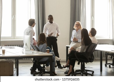 Black leader boss talk with company diverse staff at break resting after business meeting, discuss negotiations results having successful working day, corporate team communication, leadership concept