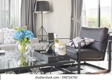 Black leather armchair and wine set on glass top table in modern living room