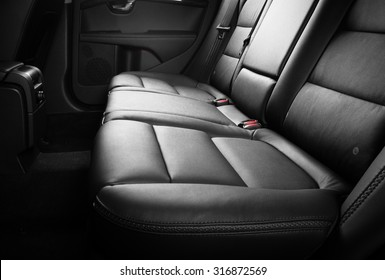 Black leather back seats inside luxury car with red seat belts plugs