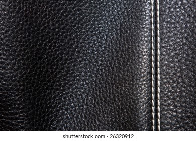 black leather background stitched up by white thread