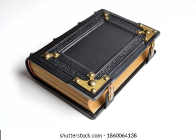 Black leather book with embossed frame and brass corners lay down to the table isolated