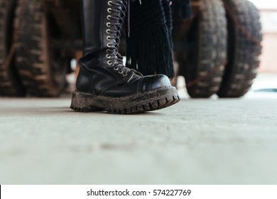 black leather boots of punk girl on industrial zone