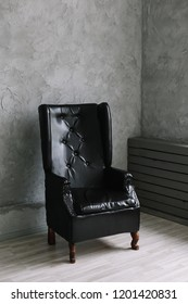 black leather chair against  gray wall background. minimalistic concept. Interior design.