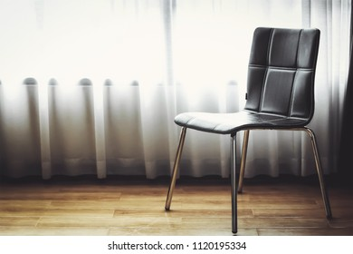 black leather chair with white curtain background