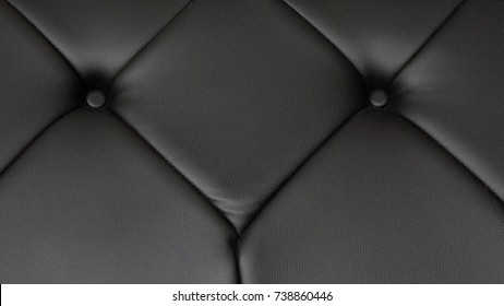 Black leather Chesterfield sofa seats close up