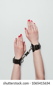 Black leather cuffs on female hands isolated on white