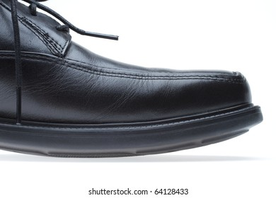 Black leather dress shoe closeup with a white background.