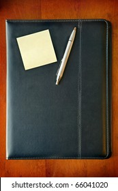 A black leather executive folder on timber desk with sticky note and silver pen
