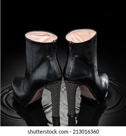 black  leather female high heel boots standing in shaking water