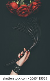 Black leather flogging whip in female hand by red roses isolated on black