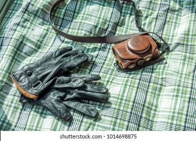 Black leather gloves and digital compact camera on green blanket. The equipments for traveler in winter.
