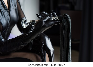 Black leather gloves and whip with fringe and handle. Mistress with a whip. Female hand hold beautiful whip close-up.