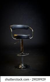 Black leather hair dresser or barber shop stool. Stage lighting with black background.