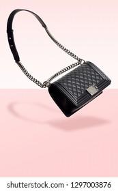 Black leather handbag on pink background. Luxury accessory