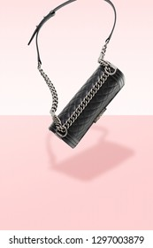 Black leather handbag on pink background. Close - up parts. Steel chain and leather belt. Luxury accessory
