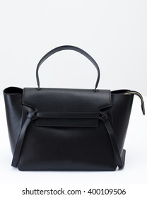 The black leather handbag on the white background