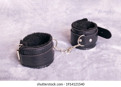 Black leather handcuffs on a gray background close up