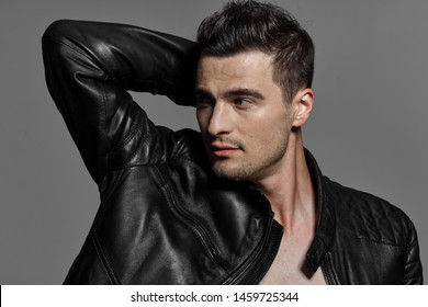 Black leather jacket nude torso sexy man raised his hand up and looks to the side