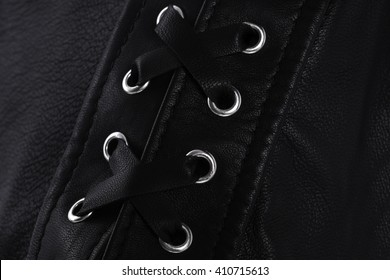 Black leather laces tight on foot / Black leather laces with chrome rings / Tight laces and black leather closeup