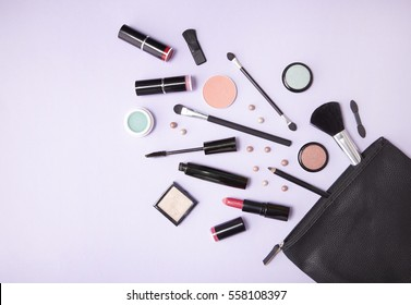 A black leather make up bag with cosmetic beauty products spilling out on to a pastel purple background, with blank space at side