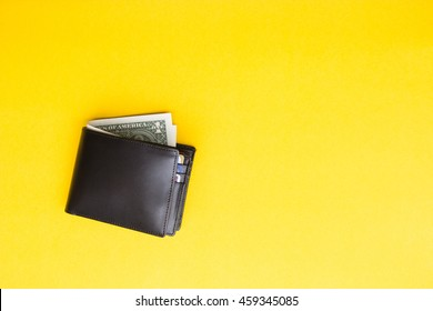 Black leather Men's Wallet with dollar cash on yellow background