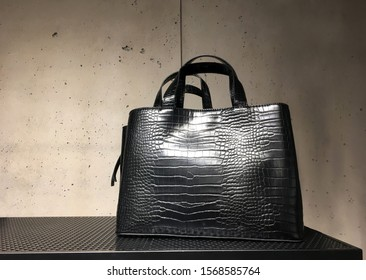 Black leather mock croc tote bag on shelf. Woman elegant handbag with two handles in a showcase of a luxury store on a concrete background. Fashion women accessories. Fashion concept