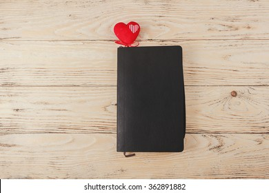 a black leather notebook is lying on a light wooden table with a cute small felt heart inside, Valentine's day accessories