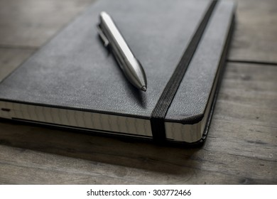 Black Leather Notebook with a Silver Pen on a Wooden Table