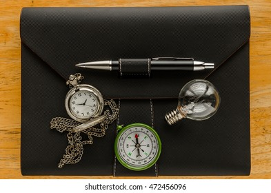 black leather organizer with compass and pocket watch ,light bulb on wooden table,key to success, concept image