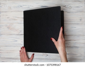 black leather photo book. photobooks on a wooden background. a person opens a photobook. a woman holds a family  photobook.
