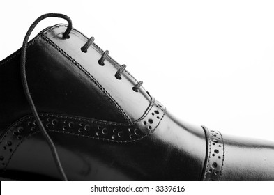 Black leather shoes against a white background