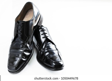 Black leather shoes with one balance on other. Shoes on white surface