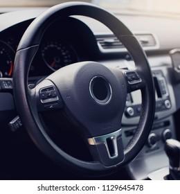black leather steering wheel closeup.