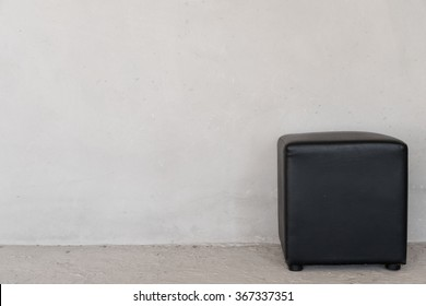Black leather stool with cement background