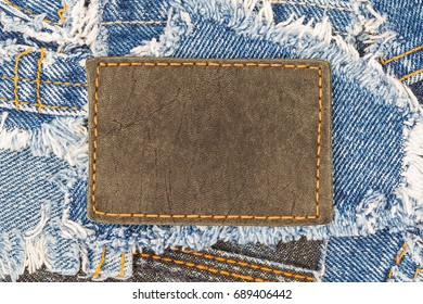 Black leather tag with orange seam on destroyed torn denim blue scraps. Leather label on ripped denim blue jeans, fashion background, close up.